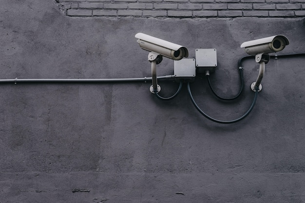 Two security cameras on a grey wall