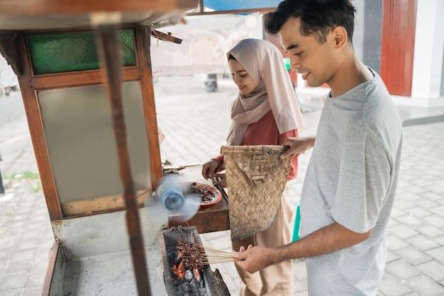 전통적인 치킨 satay를 판매하는 그들의 음식 마구간에서 음식을 준비하는 두 판매자