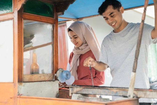 Два продавца готовят еду на своем киоске и продают традиционный куриный сатай
