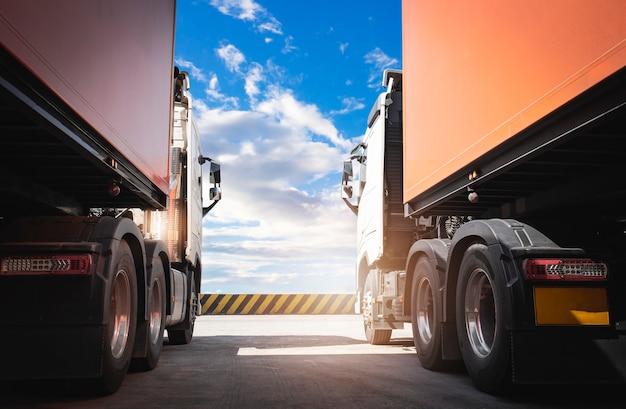 青い空の貨物貨物トラックロジスティクスと貨物輸送を備えた駐車場2台のセミトラック