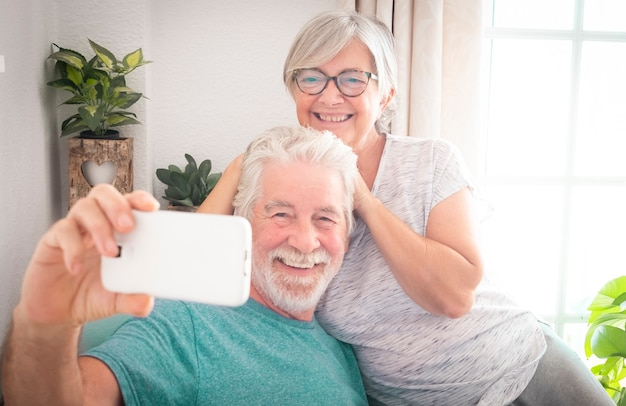 두 명의 아름다운 노인이 셀카를 위해 휴대폰을 바라보며 색깔 있는 안락의자에 껴안고 휴식을 취합니다. 긍정적인 순간. 수염과 흰 머리를 가진 남자.