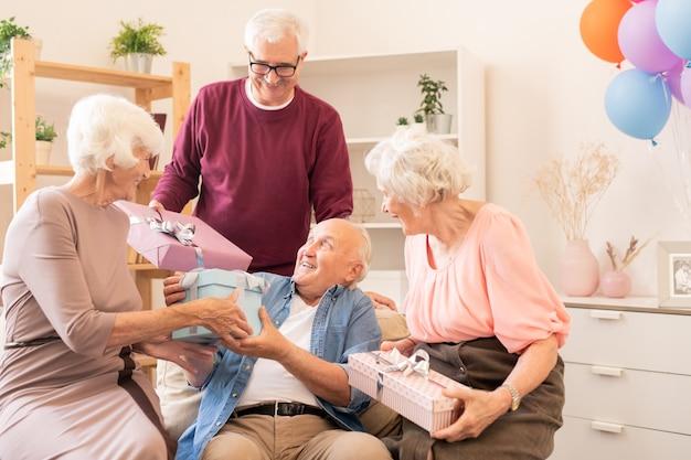 Две пожилые пары делают подарки друг другу, наслаждаясь домашней вечеринкой