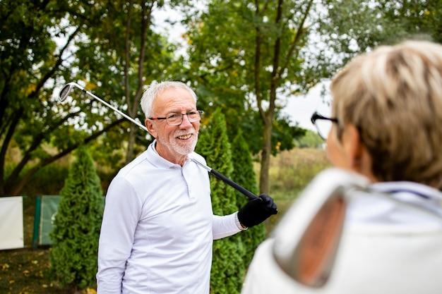 골프 훈련 전에 대화를 나누는 두 명의 시니어 골퍼.