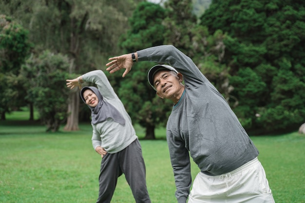 Two senior man and woman doing some stretching