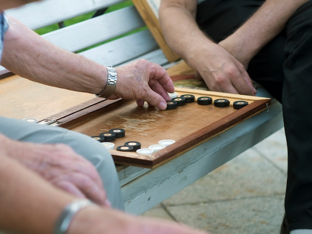 Two senior men playing backgammon on the bench in the street close up