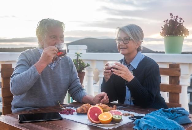 테라스에서 아침 식사를 즐기는 두 노인 남녀