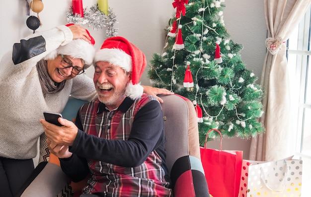 산타 모자를 쓰고 휴대폰을 즐겁게 보고 있는 은퇴한 두 사람. 백그라운드에서 선물과 크리스마스 트리