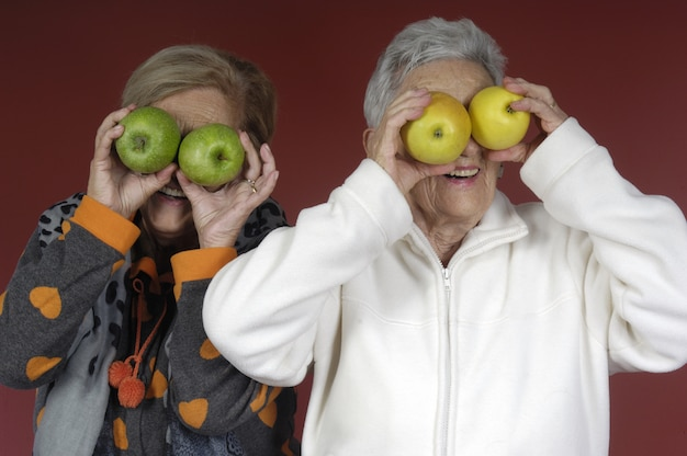 Two senior woman playing with fruits