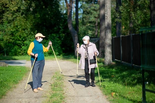 Covid-19 대유행 기간 동안 노르딕 워킹 폴과 함께 걷는 의료 마스크를 쓰고 두 노인 여성