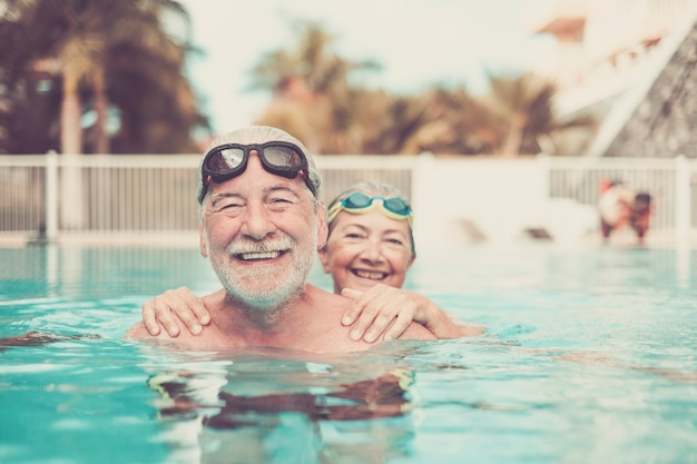수영장에서 두 명의 노인이 함께 껴안고 놀고 있습니다 - 행복한 성숙한 사람들과 카메라를 보고 웃는 연금 수령자 부부