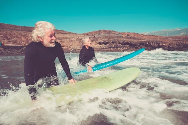 두 명의 노인이 잠수복과 서핑 보드를 들고 파도를 타거나 받는 방법을 배우기 위해 물에 들어가 여름 스포츠와 건강 및 피트니스 라이프 스타일