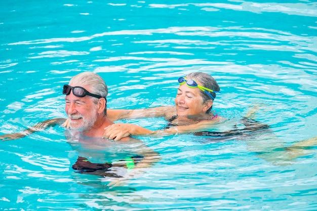 スイミングプールで一緒に2人の高齢者または成熟した白人の人々-健康のためにプールで一緒に運動しているアクティブな女性と男性-休暇の夏時間