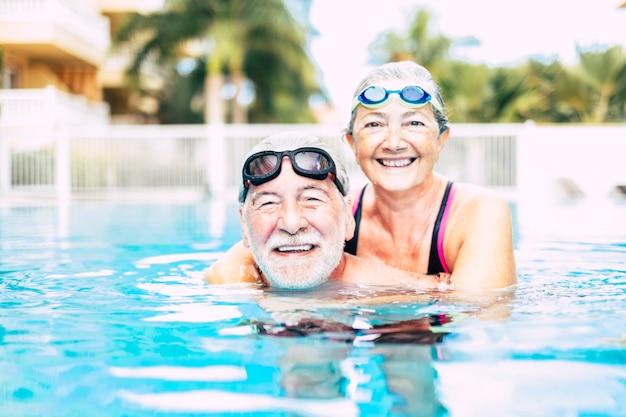 2人の先輩または成熟した人々が一緒にプールの青い水に抱きしめました-アクティブな女性と男性が一緒に運動をしています-夏の間そして楽しんでいます