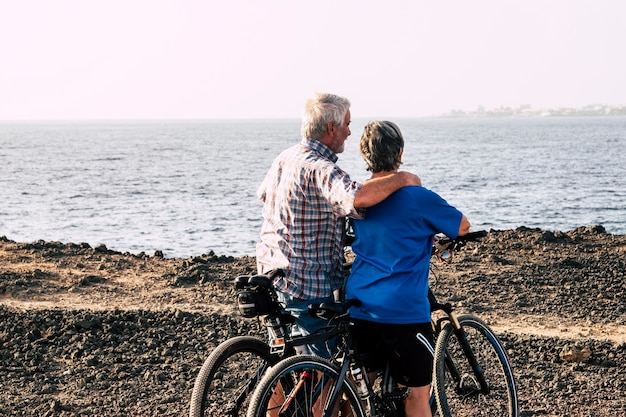 Two seniors at rocky beach with their bikes - couple of pensioners hugged together looking at the sea or ocean - healthy and fitness lifestyle