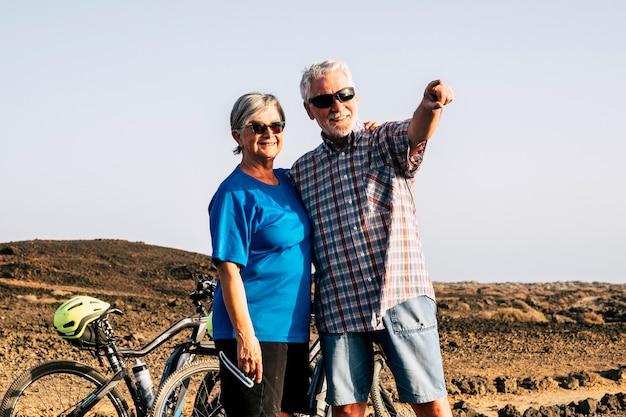 山の中で一緒に立っている2人の先輩が、自転車を背景に何かを見ていると、男が腕で何かを示しています。