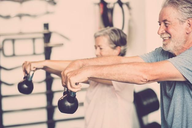 ウェイトを持ってジムで一緒に健康になるために彼女の体を働いている2人の先輩-トレーニングしている成熟した人々のカップル