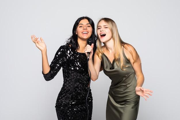 Две чувственные девушки поют с микрофоном, изолированные на белой стене