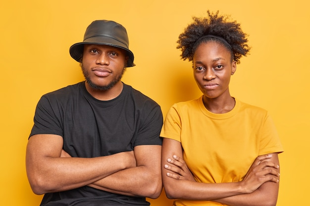 Two serious afro american brother and sister stand next to each other keep arms folded have determined expressions