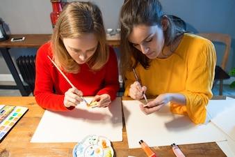 Два серьезных художника работают с кистью и палитрой