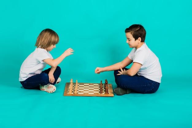 두 심각한 소년, 파란색 배경에서 체스