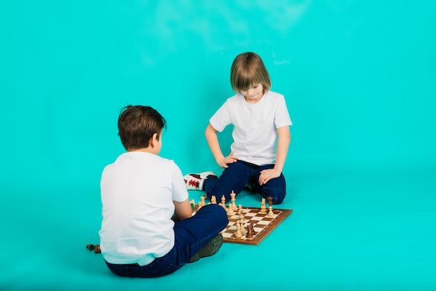 Два серьезных мальчика играют в шахматы, синий фон