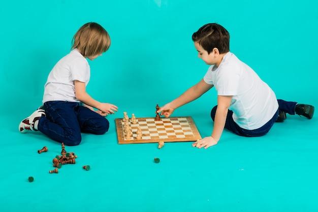 Два серьезных мальчика играют в шахматы в студии, синий фон
