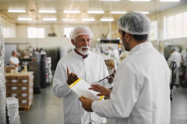 Два серьезных деловых человека в стерильной одежде, стоящие на пищевой фабрике и говорящие о бизнесе.