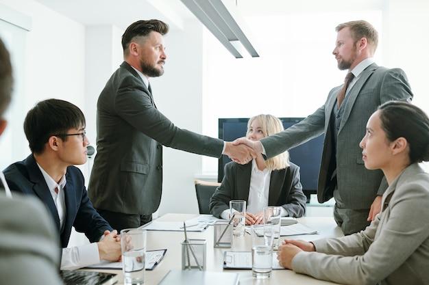 新しい契約を交渉して署名した後、同僚の間でテーブルの上で正装のハンドシェークをしている2人の真面目なビジネスパートナー