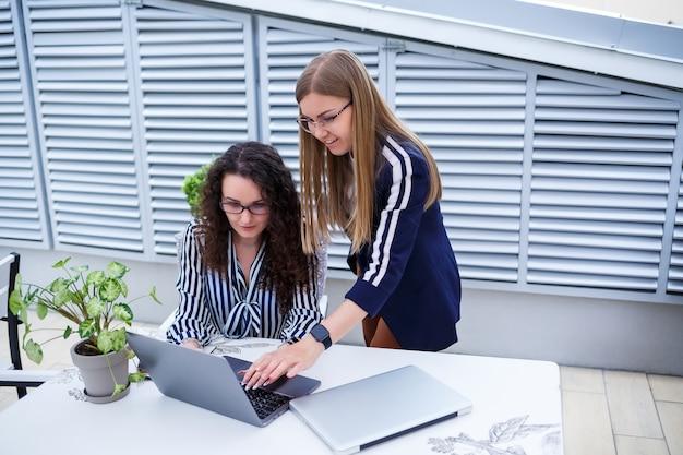Две серьезные девушки-предпринимательницы обсуждают бизнес-проект, работают вместе в офисе, серьезная женщина-консультант и клиент разговаривают на встрече, целеустремленные коллеги-руководители делятся идеями