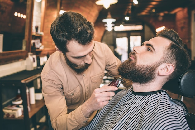 Two serious guys are in a barbershop. one of them is the customer and sitting in a chair while the hairstylist is making some magic by cutting some of the beard.