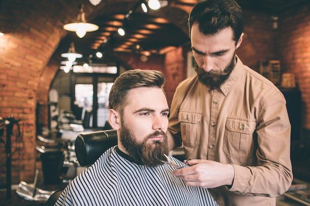 Два серьезных парня в парикмахерской. один из них - клиент, который сидит в кресле, пока парикмахер делает немного магии, подрезая часть бороды.