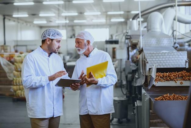 Два серьезных контролера в стерильной форме говорят о качестве соленых палочек. старший держит папку с документами, а младший держит планшет. интерьер пищевого завода.