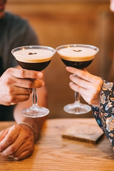Two servings of espresso coffee cocktail in tall martini glasses decorated with coffee beans.