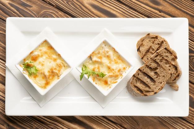 Две порции жульена с ломтиками чиабатты на гриле