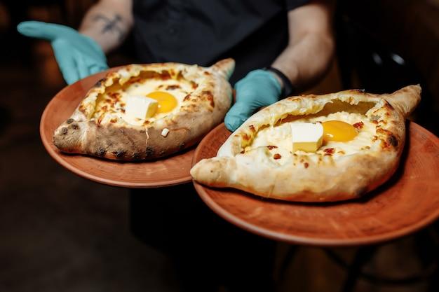 チーズとバターを使ったやわらかい柔らかい生地のハチャプリ2皿。黒い手袋をしたウェイターの手は、チーズと卵を添えた2つの伝統的なハチャプリを持っています。