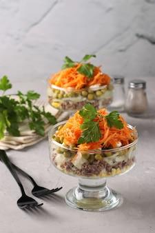 Две порции салата с корейской морковью, мясом и консервированным горошком в прозрачных салатниках на светло-сером фоне. вертикальный формат