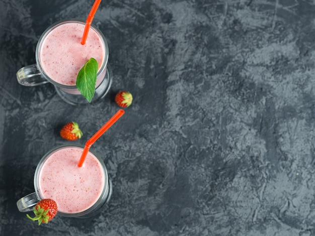 Two servings of strawberry smoothie in glass mugs on a dark table