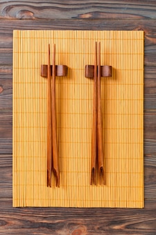 Two sets of sushi chopsticks on wooden bamboo background, top view.