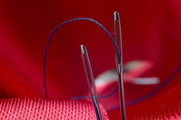 赤い布の背景に青い糸で2本のミシン針。閉じる。