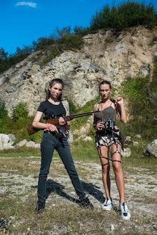자연에서 총기를 가진 두 섹시 한 아름 다운 젊은 여성. 모험