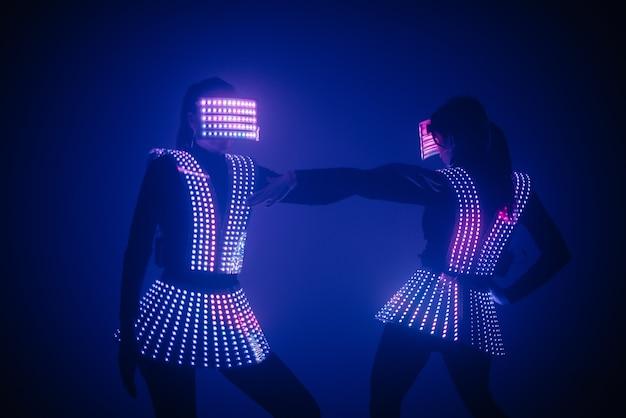 2人のセクシーなディスコダンサーがuvコスチュームで動きます。パーティーとダンス。