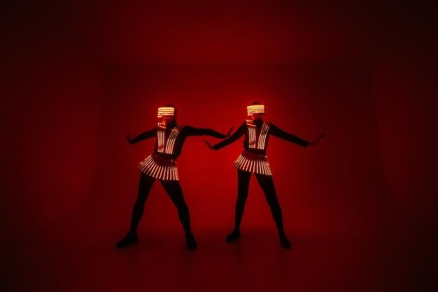 두 명의 섹시한 디스코 댄서가 Uv 의상을 입고 움직입니다. 프리미엄 사진