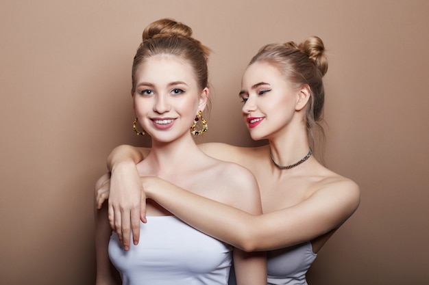 Two sexy fashion young blonde girls hugging