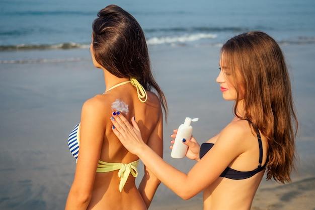 2人のセクシーな女の子がビーチで背中に日焼け止めを塗ります