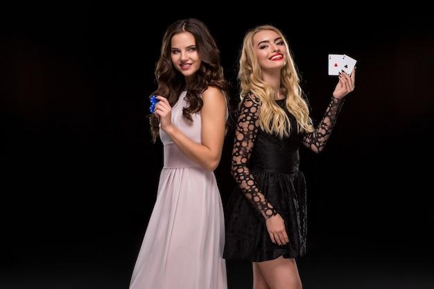 ブルネットとブロンドの2人のセクシーな女の子、手にチップとカードを持ってポーズをとる、ポーカーのコンセプト。スタジオショット。黒の背景にドレスを着た2人の美しい女性