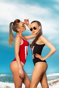 Two sexy ladies in body swimsuit on the beach