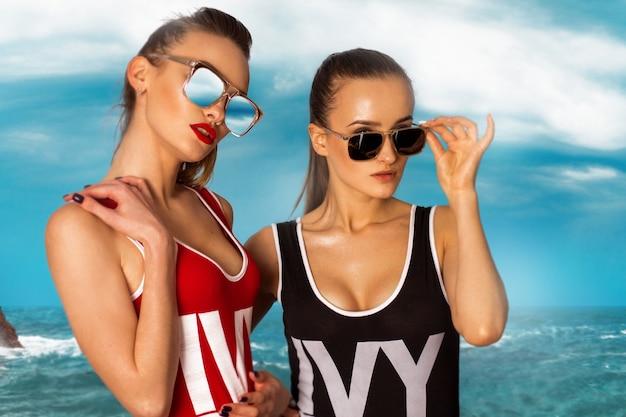 ビーチでボディ水着の2人のセクシーな女性