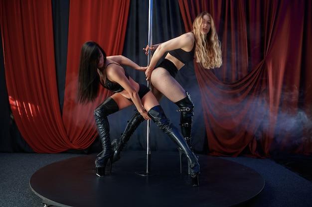 2人のセクシーなショーガール、ポールダンス、ストリップダンサー。魅力的な女性のストリッパー、ラップダンス、ポールダンスのパフォーマンス、ストリップクラブで踊る熱い女の子