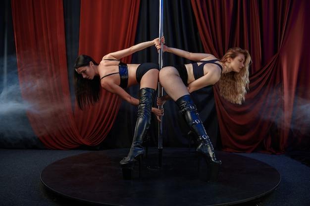 Две сексуальные танцовщицы стриптиза на сцене, танец на пилоне. привлекательные стриптизерши, танцы на коленях, выступление на пилоне, горячие девушки танцуют в стриптиз-клубе
