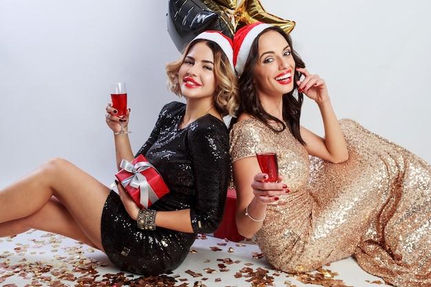 輝く金色の紙吹雪が付いている床の上に座って赤いクリスマスサンタクロースの休日の帽子で2人のセクシーな女性